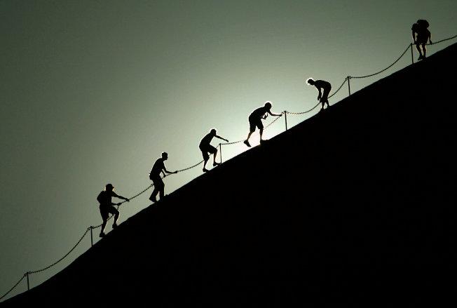 來自世界各地的遊客沿著鏈條扶手攀爬烏魯魯。(路透)