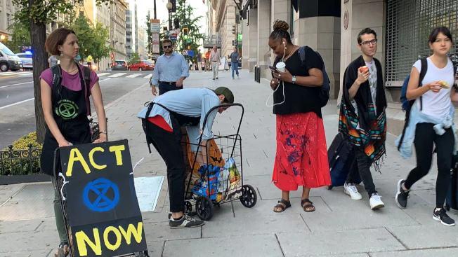 環保團體在抗議過程中還給路人發免費麵包、香蕉、蘋果等早餐,以此獲得民眾的關注和支持。(記者張筠 / 攝影)