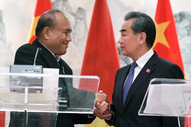 中國與吉里巴斯復交,27日在紐約簽署復交公報。圖為中國國務委員兼外長王毅(右)與吉里巴斯總統兼外長馬茂在發布會上握手。(路透)