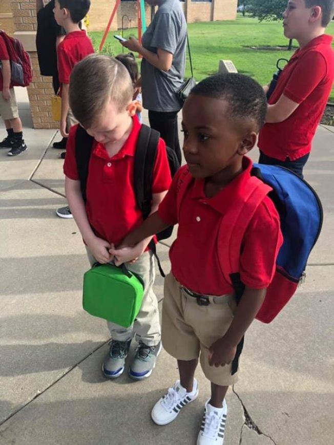 克利斯安(右)看到康諾縮在一個角落哭,主動把手伸出去握住康諾的手,一起走進學校。這張照片在網路爆紅。(取自臉書/Courtney Moore帳戶)