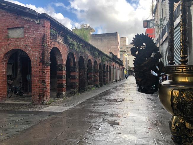 南門福德祠正面的百年街屋,赤磚洋宅,苔草斑駁,方柱拱廊,雕聯木門,淳樸古雅。