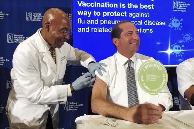 衛生官員敦促民眾趕快去打流感疫苗。圖為一名護士給衛生部長阿查爾(右)注射流感疫苗。(美聯社)