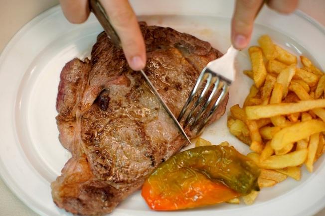 西班牙首都馬德里一處餐廳的顧客正在切牛排。各國公衛部門與醫師多年來呼籲民眾少吃牛豬等紅肉或加工肉品,以免引發心血管疾病、癌症或其他健康隱患,但最新研究公開挑戰此一幾近金科玉律的飲食規則,聲稱缺乏科學根據,對健康並無太大助益。路透