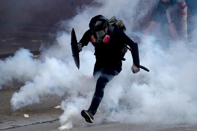 香港示威者選在十一這天大規模上街抗議,圖為抗議者在深水埗躲避港警發射的催淚彈。(路透)