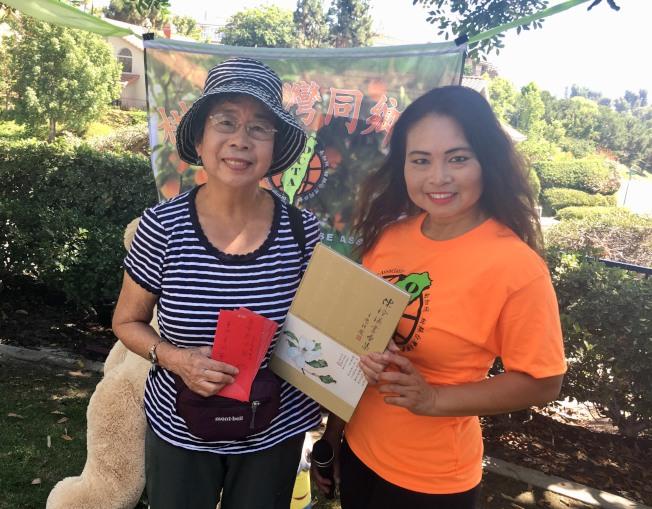 專程自紐約前來的台灣鄉親陳玲瑛,帶來自己出版創作的精美書畫集贈予會長張慧玲(右)。(記者尚穎╱攝影)