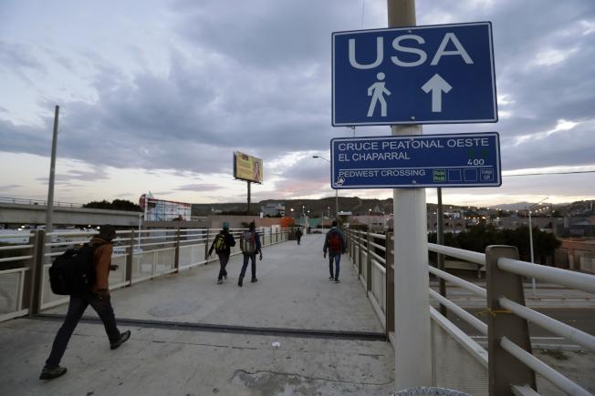 幾名移民準備從墨西哥提璜納的邊界關口進入美國。(美聯社)