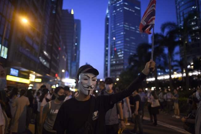 香港政府實施《禁止蒙面規例》后民眾反響激烈。圖中,一名示威者舉著英國旗子,戴著面罩反抗。(Getty Images)
