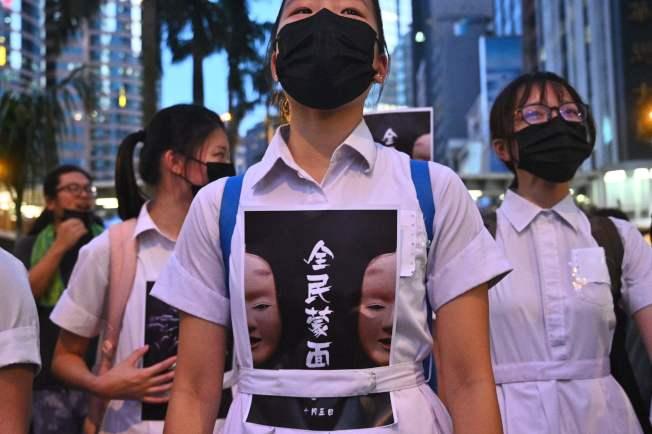 加入示威活動的香港中學生穿著寫有「全民蒙面」的衣服,戴著口罩。(Getty Images)