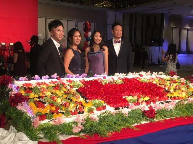 許多台僑第二代爭相與雙十國慶蛋糕合照。(記者謝雨珊/攝影)