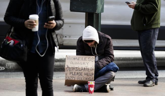遊民在紐約市街頭乞討,大多數市民習以為常。(歐新社)