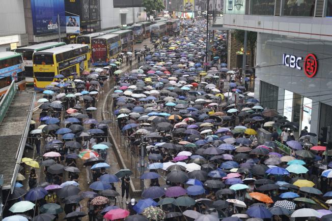大批憤怒的香港市民不畏禁令罰則,仍戴著口罩、頭盔、防毒面具等裝備,並撐著雨傘,6日自發上街遊行,表達對港府的不滿和抗議。(美聯社)