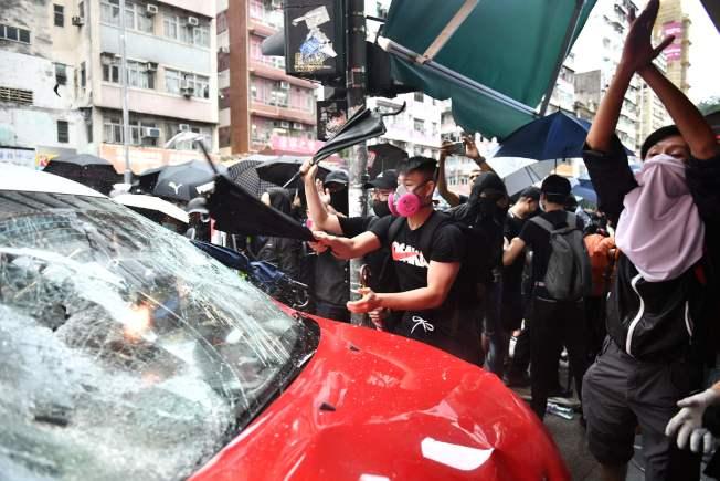 部分香港民眾6日不懼禁令,仍戴面罩口罩走上街頭抗議。圖為示威者在街頭暴砸車輛。(Getty Images)