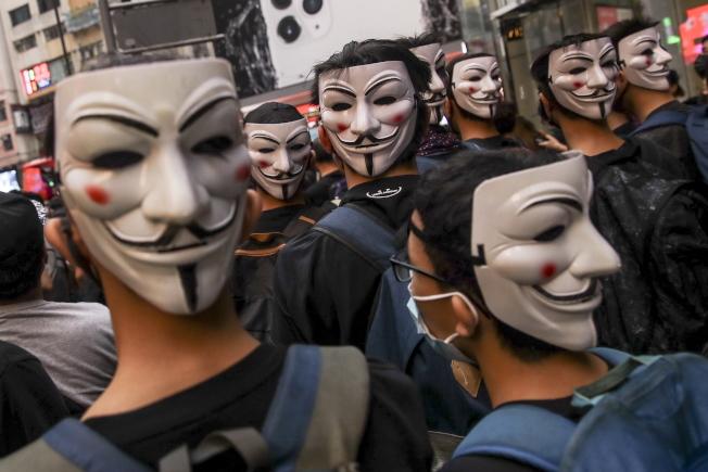 港府強推「禁蒙面法」的第二天,部分民眾不懼禁令,仍戴著「V怪客」面具,走上街頭,四處表達抗議。(歐新社)
