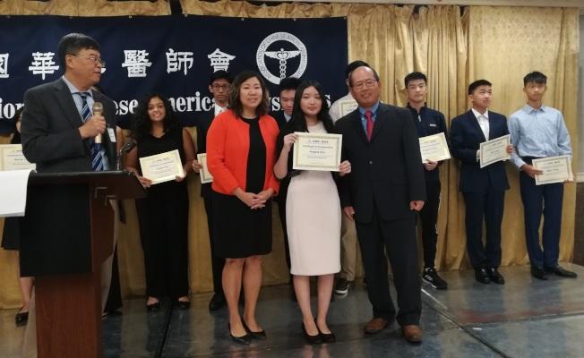 孟昭文(红衣者)为金奖获得者Angela Zhu(前排右二)颁奖。(华人医师会提供)