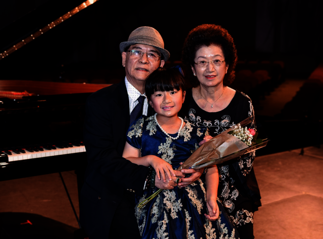 黃以欣(中)與特別由中國趕回來參加音樂會的書法大師外公王岩平(左)和外婆合影。(Patrick Wong攝影)