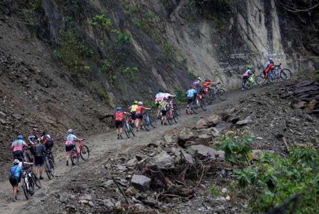 「死亡公路」地形險峻,許多選手受不了只能牽車上坡。(路透)