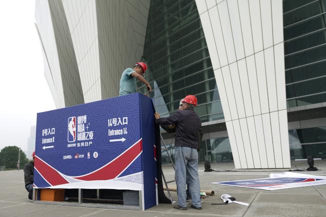 中國中央電視台宣布取消轉播兩場NBA季前賽後,上海東方體育中心也取消球迷見面會。圖為工作人員正在拆除看板。(美聯社)