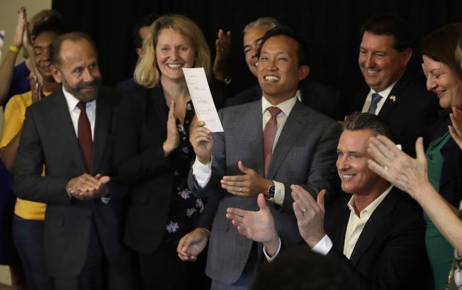 邱信福(右三)高舉紐森(坐者)簽署的AB1482法案,右艾金斯。(美聯社)