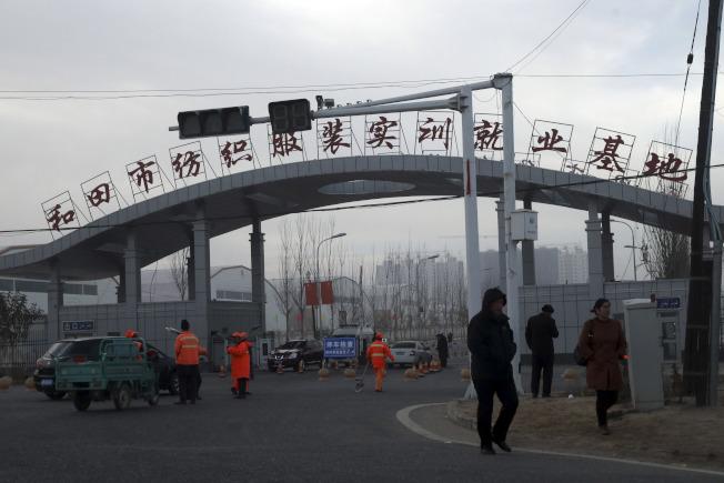 新疆和田泰達服裝公司被控雇用再教育營的維吾爾勞工,被美國列入制裁名單。圖為和田市紡織服裝實就業基地的大門。(美聯社)