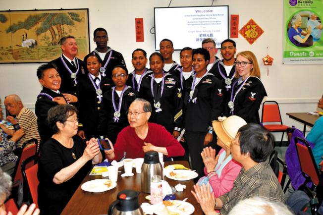 14名海軍官兵來到華埠建民中心當義工派餐,受到現場耆英長者鼓掌歡迎。(記者黃少華╱攝影)