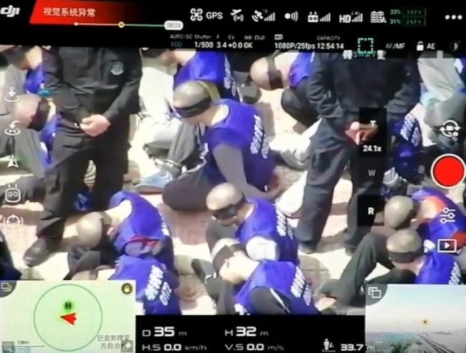 一支似是在中國新疆拍攝的無人機影片近日被人上傳網路,可見到數百身穿「喀什巿(Kashgar)拘留中心」字樣背心的男子被特警押下火車,在火車站外的廣場席地而坐。放大的影片則顯示,這些人頭髮被剃光,眼睛被黑色眼罩蒙住,雙手則被綁在背後。(取材自YouTube)