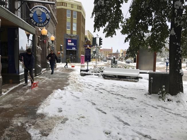 秋季暴風雪肆虐洛磯山脈地區,蒙大拿州海林那(Helena)地區商家9日在風雪過後,清掃店前道路。(美聯社)