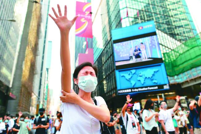 香港反送中抗爭持續,社會爭議與紛擾對港人精神健康出現負面影響。圖為香港民眾戴口罩上街抗議。(法新社)
