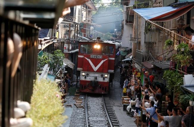 遊客聚集到越南老城區知名觀光景點「火車街道」,拍攝火車慢速通過。路透
