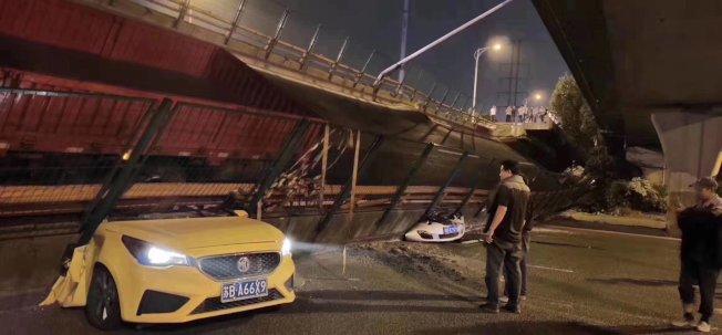 一位民眾正看著被高架橋壓跨的轎車。圖/漢森供應鏈董事長黃剛微博