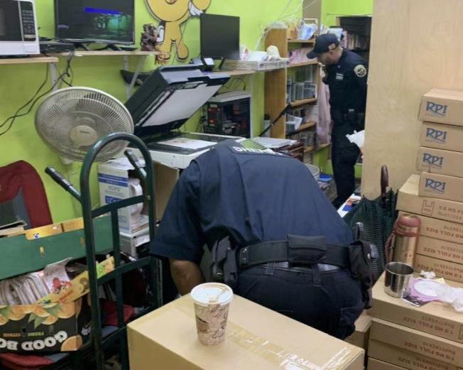 執法人員在華人攤位裡尋找私菸。(讀者提供)