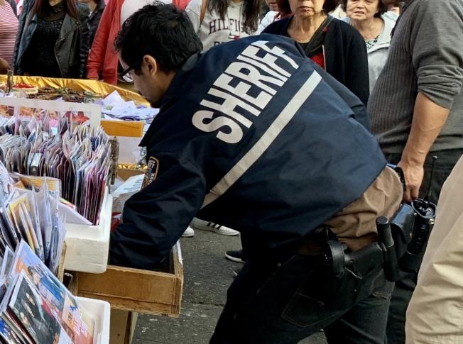執法人員在尋找私菸。(記者朱蕾/攝影)