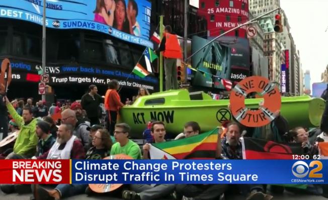參加氣候變遷抗議示威的群眾把一艘綠船運到時報廣場。(WCBS電視頻道截頻)