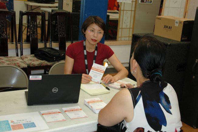 人口普查局職員楊小姐(後)現埸為申請人作講解及幫助申請等服務。