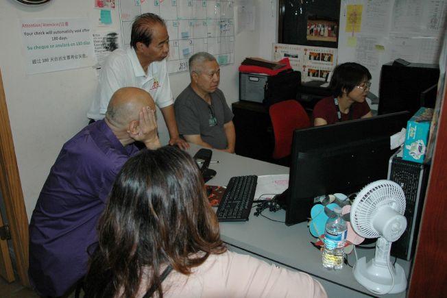 人口普查局職員楊小姐(右)、廣州協會常務理事長容蔭寧(站立)為申請人網上登記。