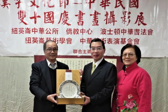 中華書法會會會林卓培(左)、 周麗桃(右) 贈送手工藝製作書畫瓷器盤藝術品給施維鈞(中) 。(記者薛劍童/攝影)
