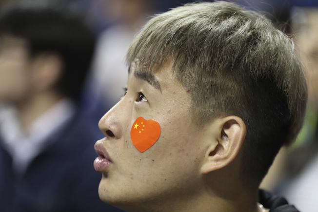NBA上海賽事,儘管球場禁止攜帶旗幟入場,仍有球迷在臉上貼上小型五星旗,表達政治立場。(美聯社)