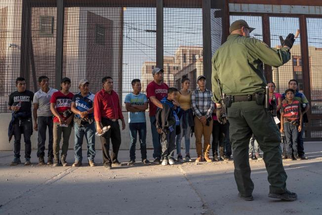 川普政府積壓的移民案件愈來愈多,數量已逼近百萬。圖為越過邊界的中美洲無證移民,在邊界等候前往移民處理中心。(Getty Images)