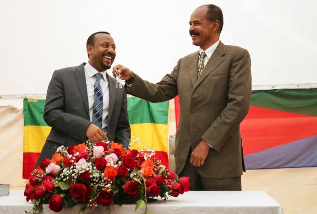 衣索比亞總理艾比伊(左)11日獲得諾貝爾和平獎殊榮,表彰他促成與厄利垂亞解決邊界爭議,達成和平協議的努力。圖為厄立垂亞總統伊薩亞斯(右)在厄國駐衣國大使館成立典禮上,拍拍艾比伊肩膀。(路透)