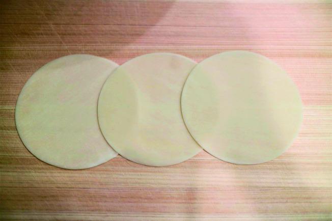 玫瑰花煎餃包法 1.取3張餃子皮稍微重疊,在接縫處用水將餃子皮黏接在一起。
