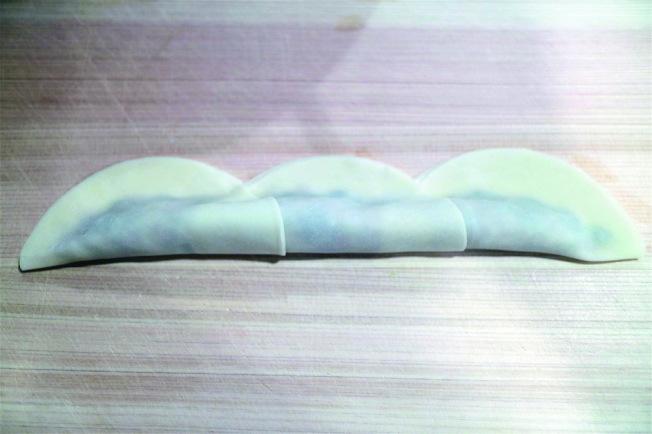 玫瑰花煎餃包法 3.將餃子皮往上對折,用水將對折處黏起來固定好。