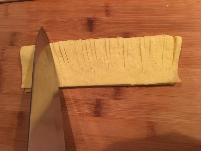 2.把蛋餅修成長方形,對折後切3毫米左右的條,不要切斷。