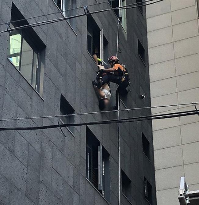 消防員正在解救倒掛窗外的女子。(取材自海外網)