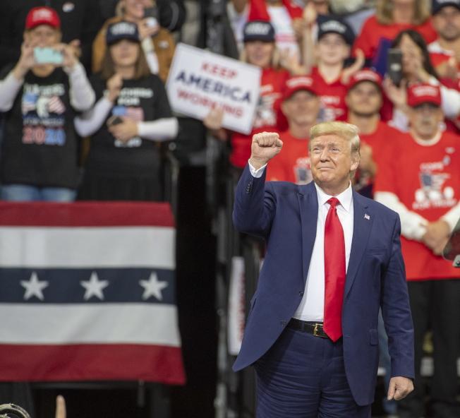 川普為擺脫彈劾案的陰影,到明尼蘇達州競選造勢,並向支持者舉拳示意。(歐新社)
