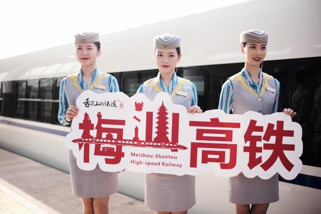 梅汕鐵路11日開通運營,圖為列車員歡迎旅客乘車出行。(中新社)