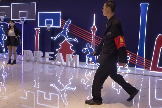 NBA深圳季前賽在當地12日晚登場,警方戒備如臨大敵。圖為北京公安走過一面畫有籃球競技的牆。(美聯社)