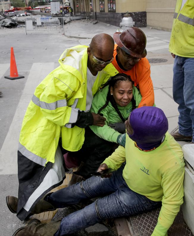 紐奧良興建中的硬石酒店部分建築12日上午坍塌,造成至少1死18傷;事故發生後,工人在現場照顧傷者。(美聯社)
