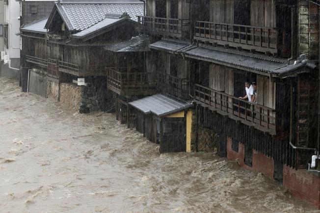 哈吉貝颱風侵襲日本,三重縣伊勢市的五十鈴川河水暴漲,民眾12日憂心地看著湍急水流。(美聯社)