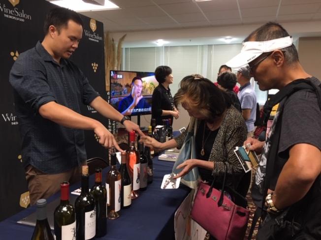 Kanpai Wines執行總裁暨Napa Valley Meadowbrook Farm莊園園主,以及「神之雫品酒沙龍」北美市場負責人姜理得(Peter Chiang,左),在旅遊展上向民衆解釋各種葡萄酒製作和特點。(記者楊青/攝影)
