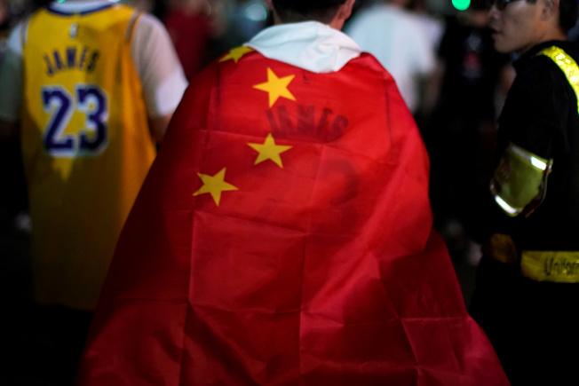 上海和深圳的NBA中國賽如期舉行,但場內外不少中國球迷將五星旗披在身上。(路透)