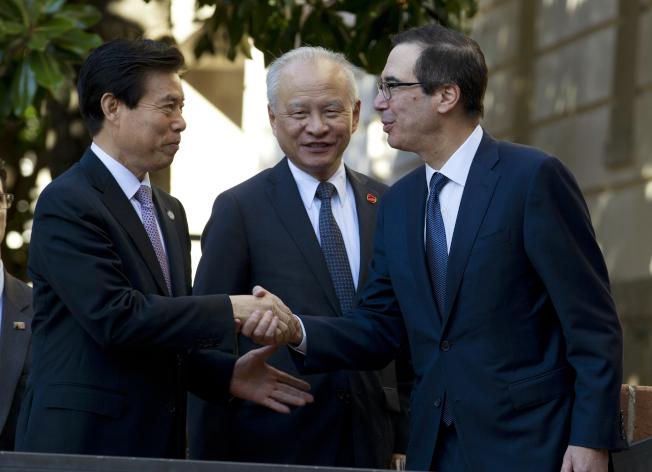 美中達成初步貿易協議後,美國財政部長米努勤(右)與中國商務部長鍾山握手,中為中國駐美大使崔天凱。(美聯社)